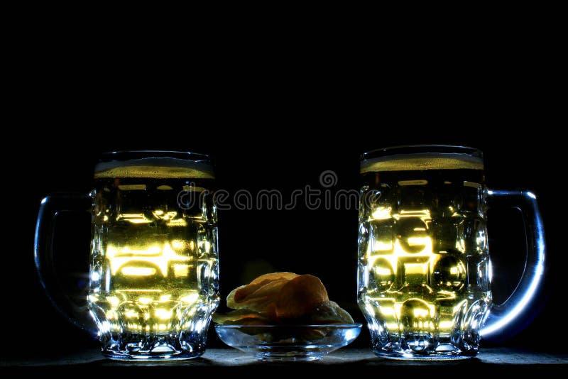 Öl två rånar och potatischiper mot svart bakgrund royaltyfri fotografi