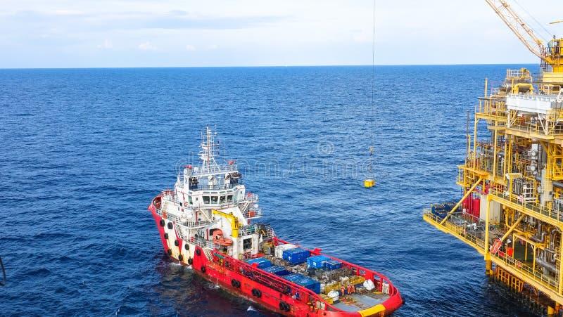 Öl und Gas, die Plattform, anhebende Fracht des Kranes zum Laden zum Versorgungsschiff verarbeiten stockbilder