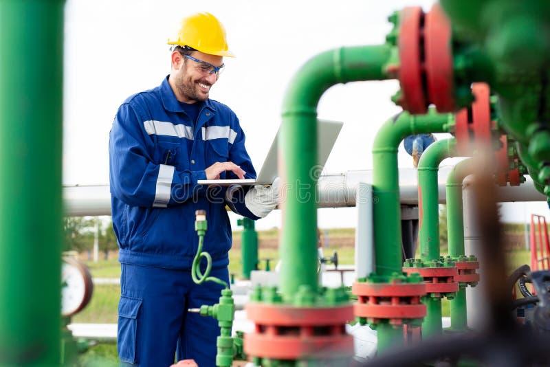 Ölarbeiter, der portables Radio und Laptop verwendet lizenzfreie stockfotografie