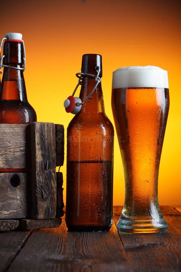 Ölexponeringsglas och ölback med flaskor royaltyfri foto