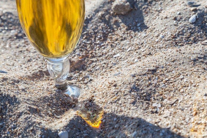 Ölexponeringsglas på sanden royaltyfria foton