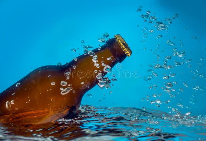 Ölflaska i vatten arkivbilder