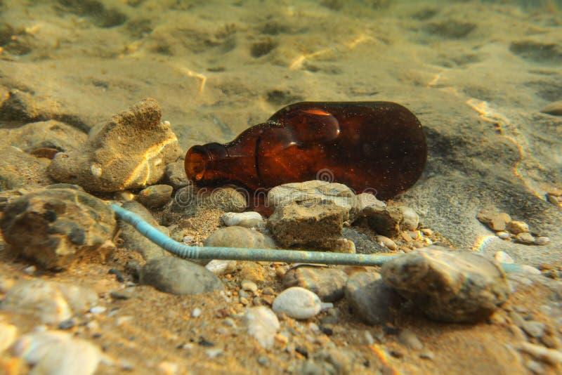 Ölflaska- och plast-sugrör på sandhavsbotten Undervattens- pho royaltyfri foto
