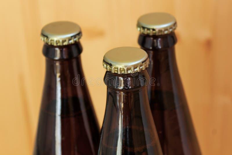 Ölflaskor kyld drinknärbild, på träbakgrund arkivfoton