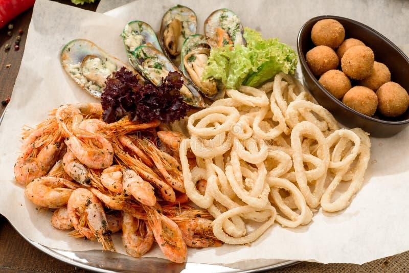 Ölmellanmål: lökcirklar, musslor i en krämig sås, stekte räkor och ostbollar på hantverkpapper på ett magasin arkivfoto