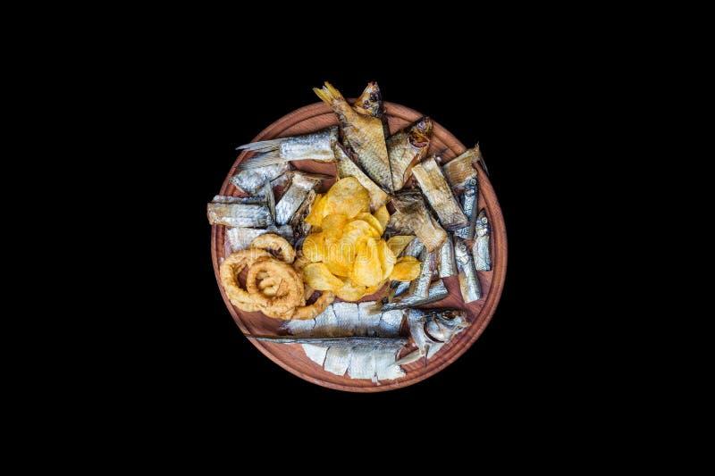 Ölmellanmåluppsättning Den saltade torkade fisken, tioarmad bläckfiskcirklar och potatischiper, tjänade som på skärbrädan royaltyfria foton