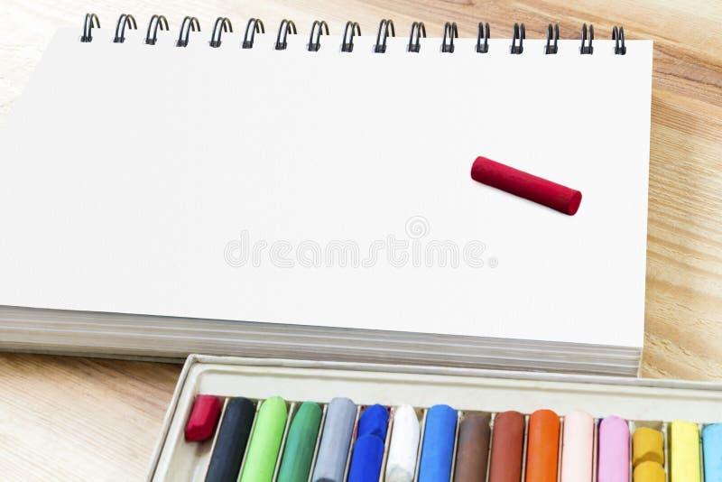 Ölpastellkunstsammeln für die Kunst, die auf Papierbuch und Satzkasten bunte Zeichenstifte auf hölzernem Tabellenhintergrund mit  lizenzfreie stockbilder