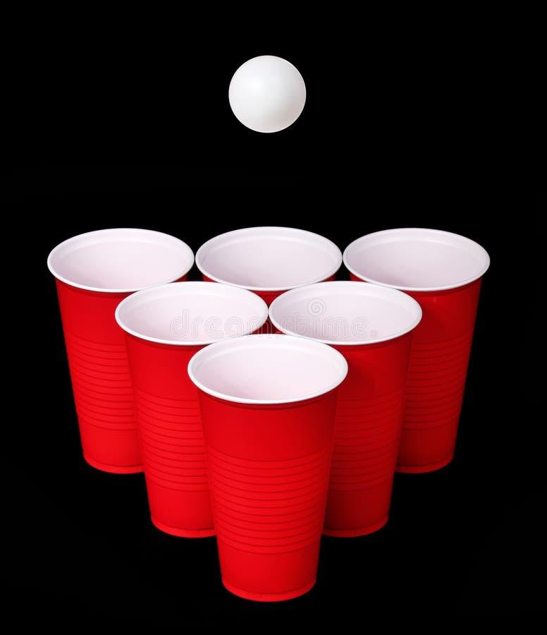 Ölpong. Röda plast-koppar och knackar pongbollen över svart fotografering för bildbyråer