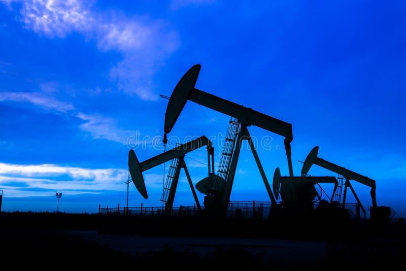 Ölpumpen am Ölfeld mit Sonnenunterganghimmelhintergrund lizenzfreie stockfotos