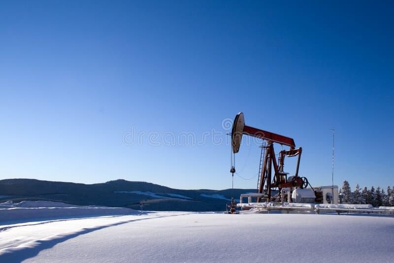 Ölquelle pumpjack Gebirgsschnee stockbild