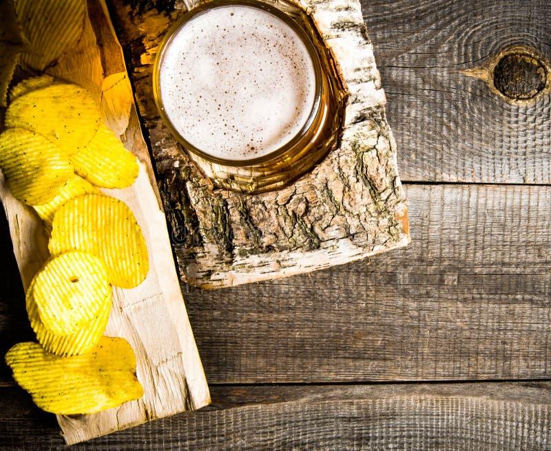 Ölstilen Exponeringsglas av öl på björkställning och chiper på träbakgrund royaltyfri bild