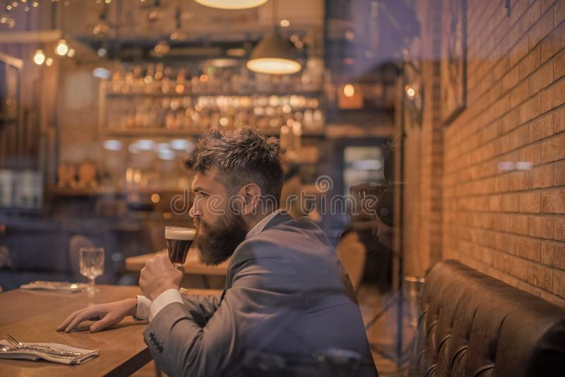 Öltid Affärsman med den långa skäggdrinken i cigarrklubba den allvarliga stångkunden sitter i kafé som dricker öl Datummöte royaltyfri bild