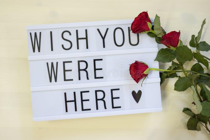 Önskaen var du här skriftlig på en lightbox med rosor arkivbilder