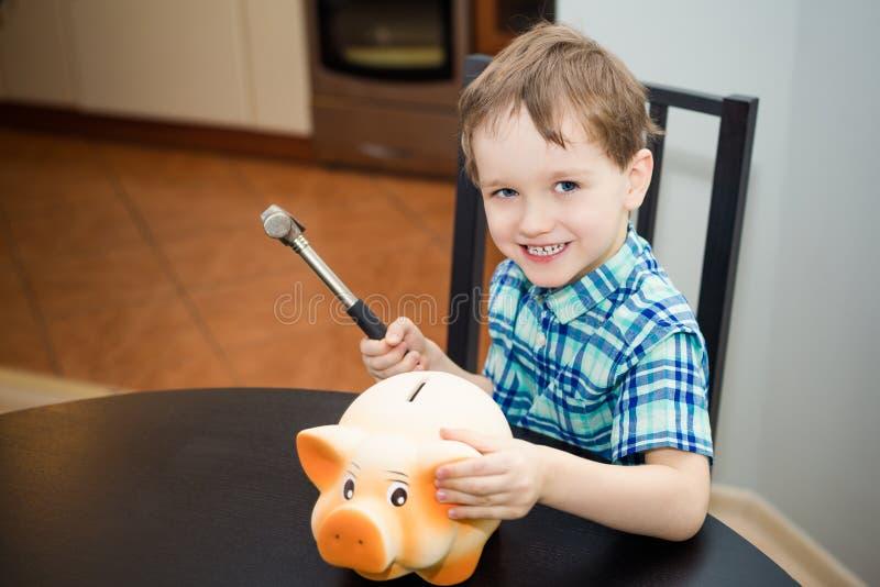 önskar årig pojke 4 att bryta spargrisen arkivfoto