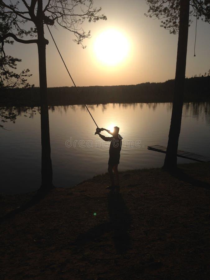 Önskar den härliga naturpojken för solnedgången på sjön att hoppa med repet fotografering för bildbyråer