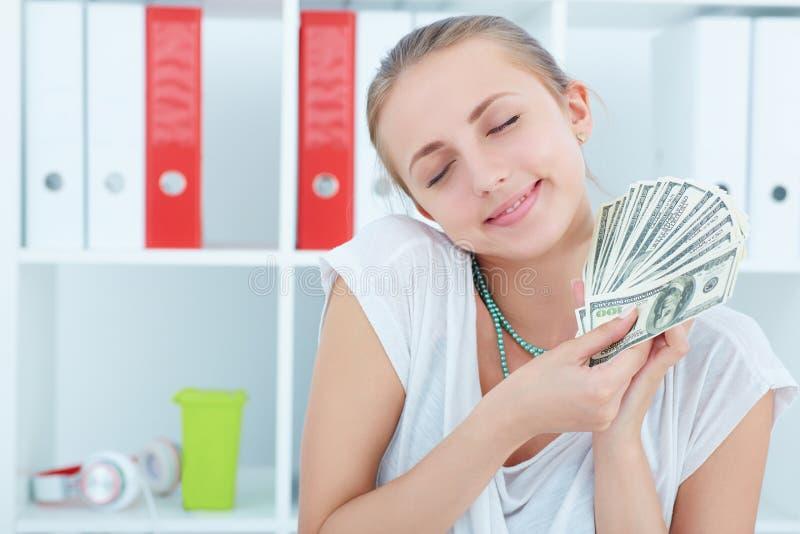 Önskar hållande dollar för lycklig kvinna i händer och att spendera pengar arkivfoton