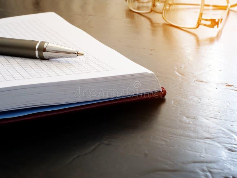 Öppen anteckningsbok med pennan och exponeringsglas Påminnelse på skrivbordet royaltyfri bild