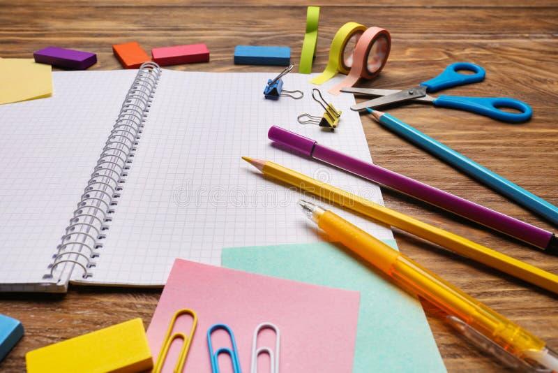 Öppen anteckningsbok med skolabrevpapper på träbakgrund fotografering för bildbyråer