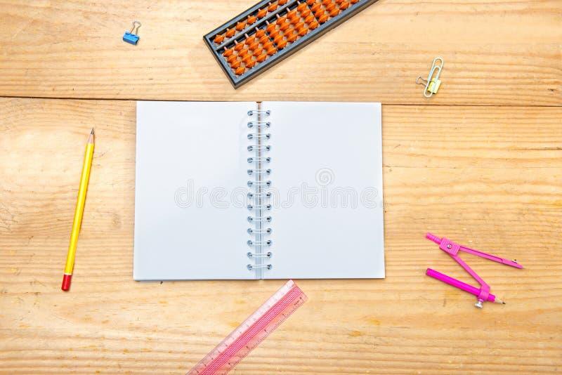 Öppen anteckningsbok med skolatillförsel och brevpapper på trätabellen arkivbild