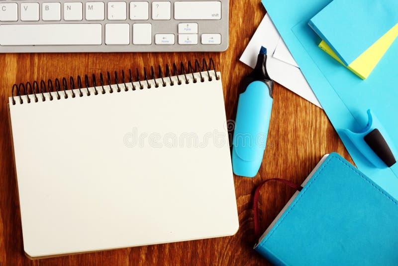 Öppen anteckningsbok med tillbehör för tom sida och kontors royaltyfri fotografi