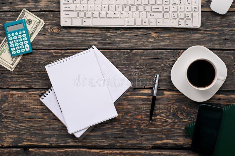Öppen anteckningsbok med tomma sidor, penna, räknemaskin, tangentbord, pengar arkivbild