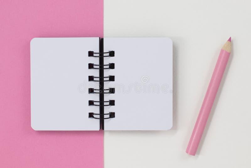 ?ppen anteckningsbok och rosa blyertspenna, p? rosa och vit bakgrund royaltyfri fotografi
