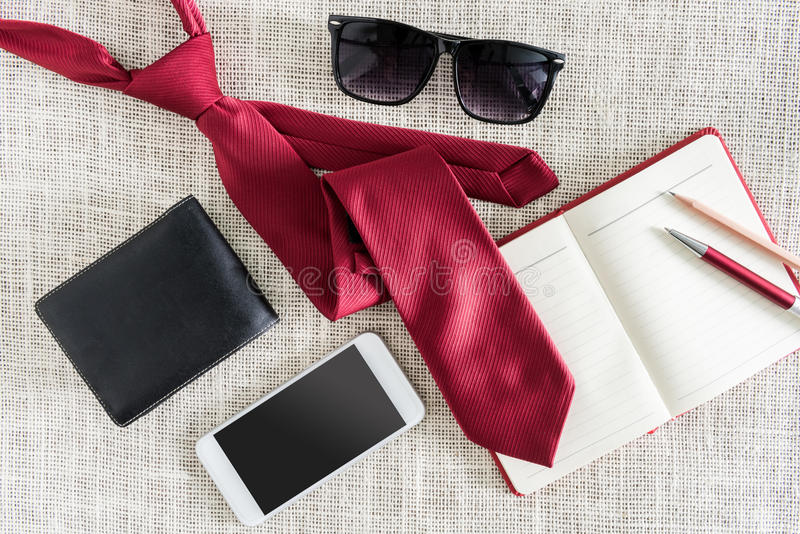 Öppen anteckningsbok, penna, blyertspenna, smartphone, plånbok, solglasögon på cl arkivbild