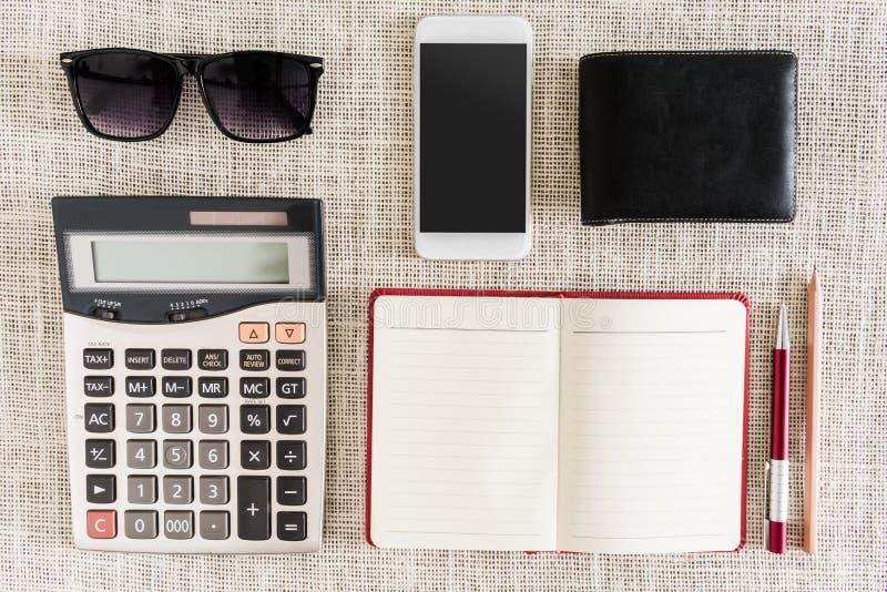 Öppen anteckningsbok, penna, blyertspenna, smartphone, plånbok, solglasögon på cl arkivfoton
