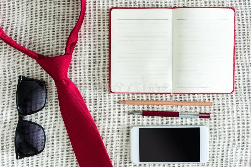 Öppen anteckningsbok, penna, blyertspenna, smartphone, solglasögon på den rena säcken royaltyfria foton