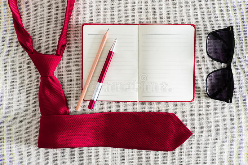 Öppen anteckningsbok, penna, blyertspenna, solglasögon på ren säckväv med r fotografering för bildbyråer