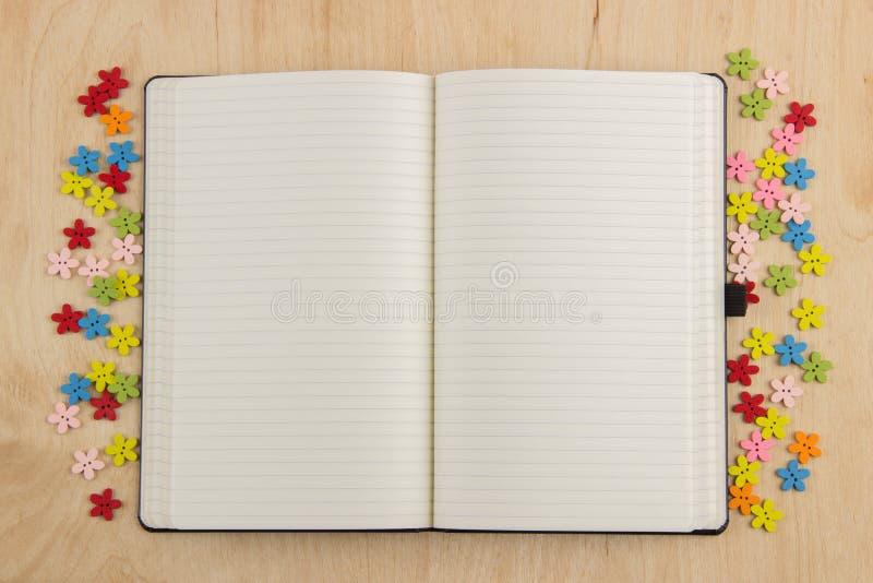 Öppen anteckningsboksidaneedlewoman med knappar, tråd, blommor och royaltyfria bilder
