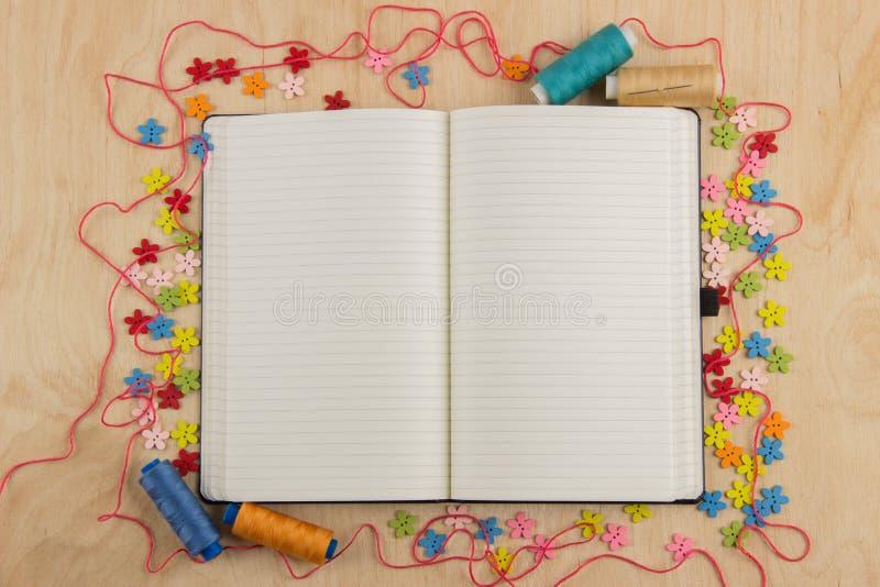 Öppen anteckningsboksidaneedlewoman med knappar, tråd, blommor och royaltyfri foto