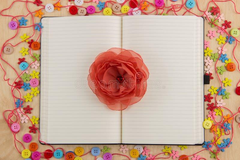 Öppen anteckningsboksidaneedlewoman med knappar, tråd, blommor och arkivfoto