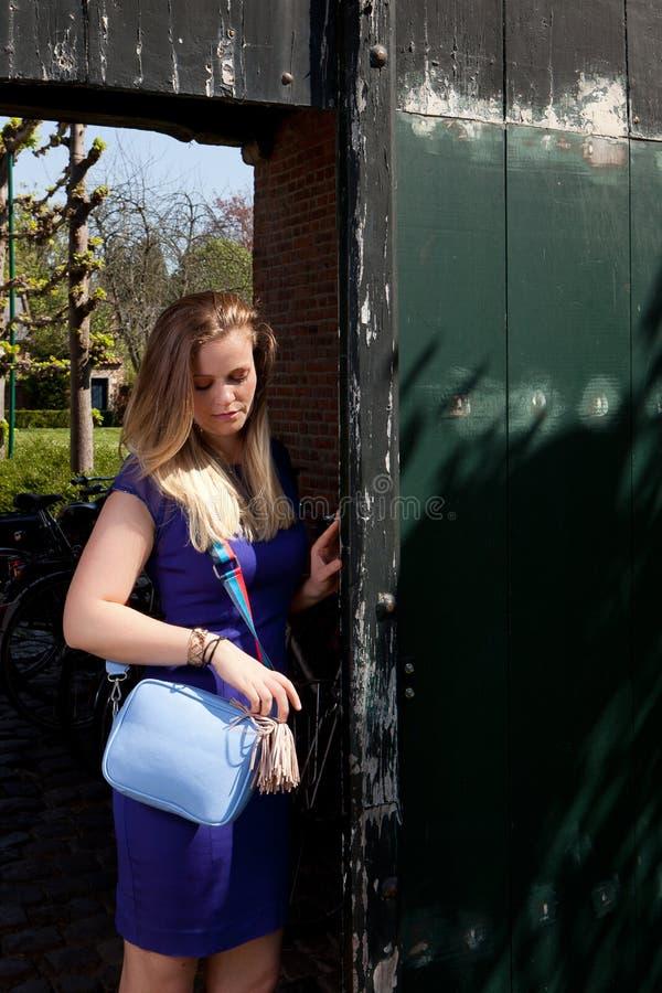 Öppen antik dörr för blond kvinna, Groot Begijnhof, Leuven, Belgien fotografering för bildbyråer