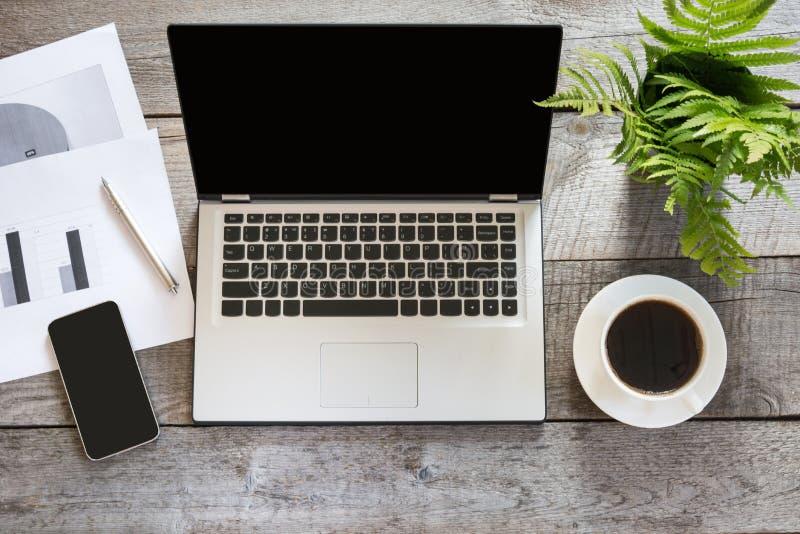 Öppen bärbar dator med dokumentation på kontorsträskrivbordtabellen Top beskådar royaltyfri foto