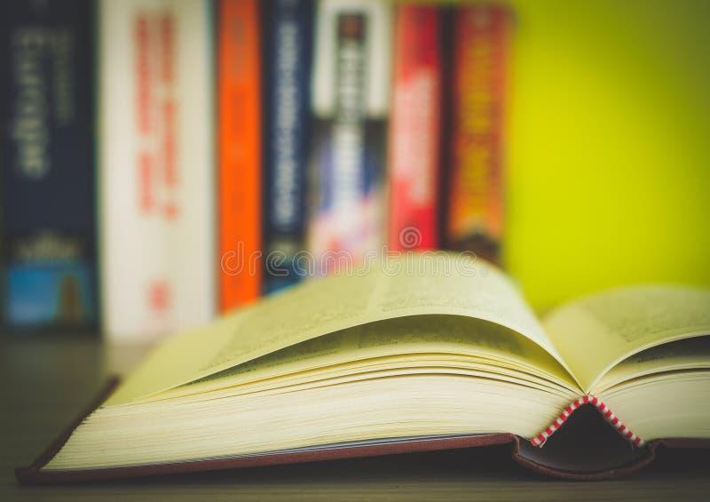 Öppen bok, bunt av färgrika inbunden bokböcker som isoleras på vit bakgrund tillbaka skola till Kopiera utrymme för text tonad bi arkivfoton