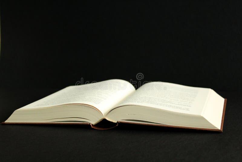 Öppen bok för tappning, svart bakgrund, sidosikt, svart bakgrund royaltyfri foto