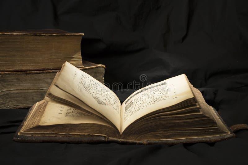 Öppen bok med den ljusa strålkastaren på text med böcker på bakgrund royaltyfri fotografi