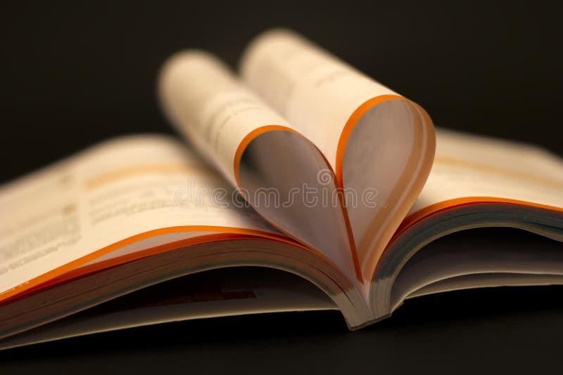 Öppen bok med hjärtaformsidan på den svarta tabellen Utbildningsbakgrund, tillbaka till skolabegreppet arkivbilder