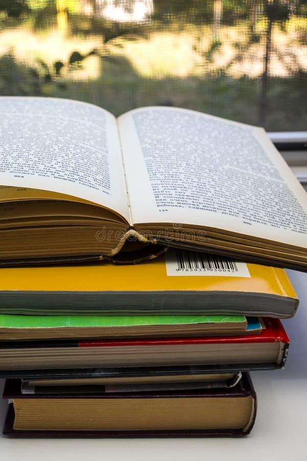Öppen bok och många böcker på tabellen fotografering för bildbyråer