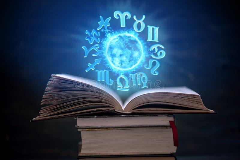 Öppen bok på astrologi på en mörk bakgrund Det glödande magiska jordklotet med tecken av zodiaken i det blåa ljuset arkivfoto