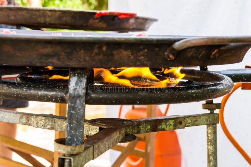 Öppen brandflamma av gasgasbrännaren med den stora plana paellajambalayastekpannan med matlagningmål Utomhus helgpicknick royaltyfri bild