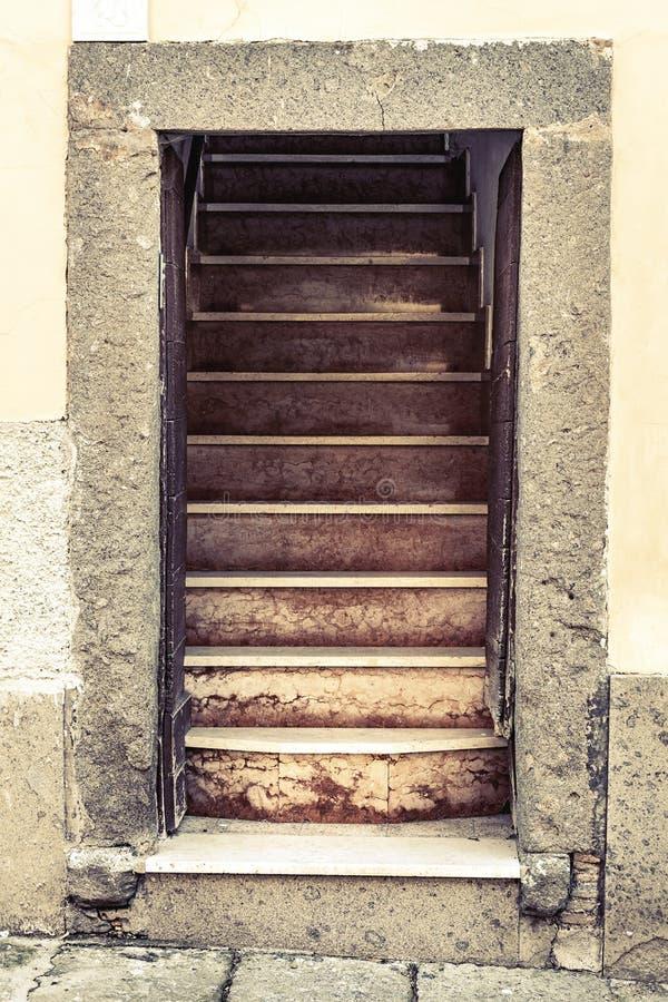 Öppen dörr för gammalt ingångsstenhus med trappa royaltyfri foto