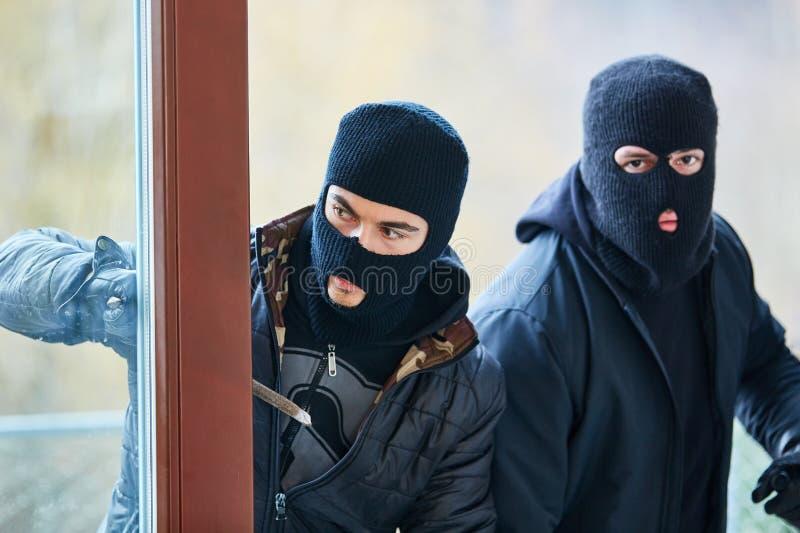 Öppen dörr för två inbrottstjuvar under inbrott arkivbilder