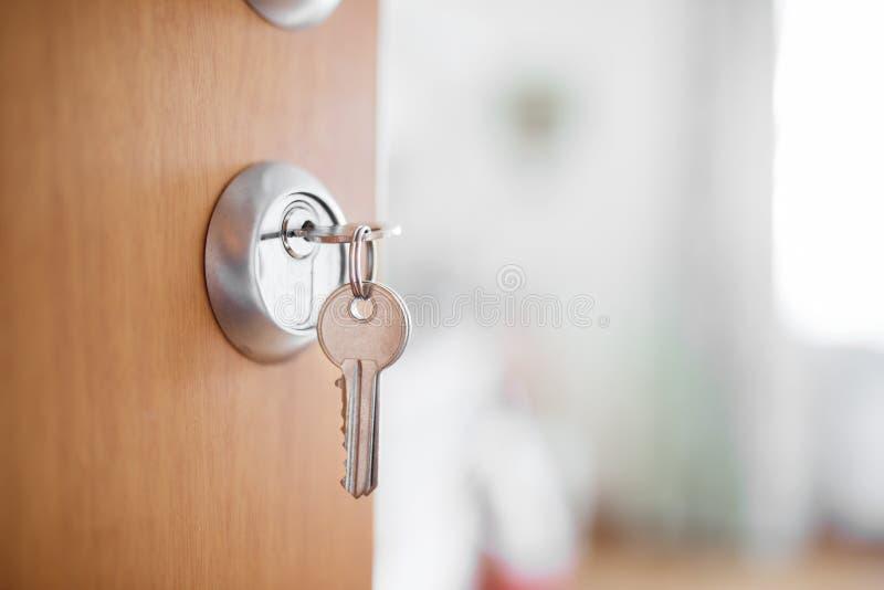 Öppen dörr med tangenter, tangent i nyckelhål arkivbild
