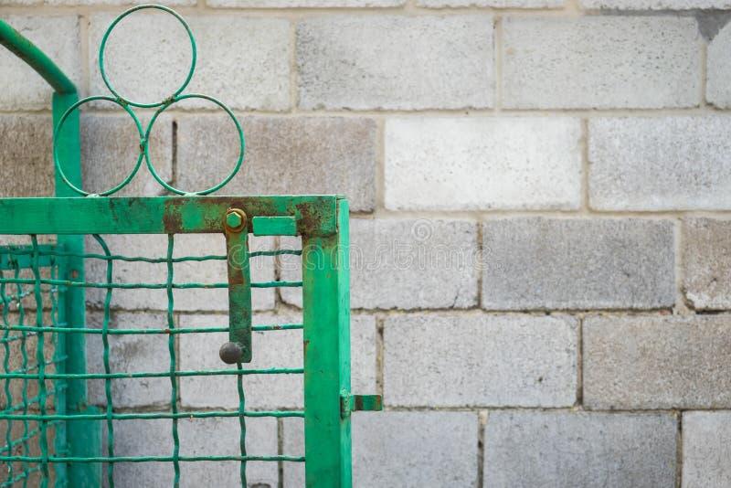 Öppen grön port och staket för svetsat ingrepp mot en vägg av askakvarteret royaltyfri fotografi