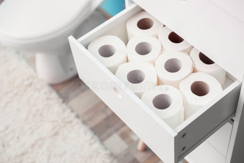 Öppen kabinett enhet med pappers- rullar för toalett royaltyfria foton