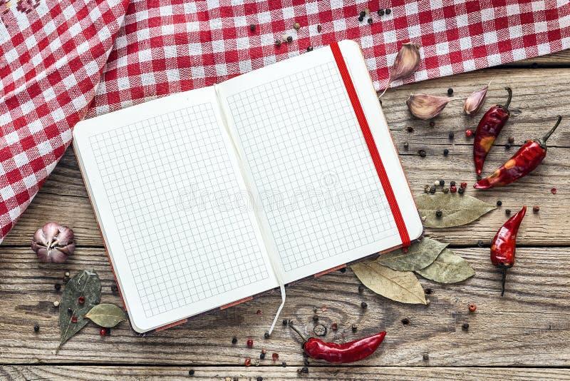 Öppen kokbok för mellanrum med smaktillsatser och en rutig servett på royaltyfri bild