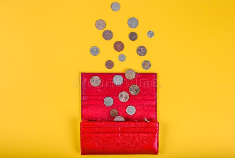 Öppen kvinnlig röd läderplånbok med olika mynt på gul bakgrund med kopieringsutrymme, över huvudet sikt royaltyfria foton