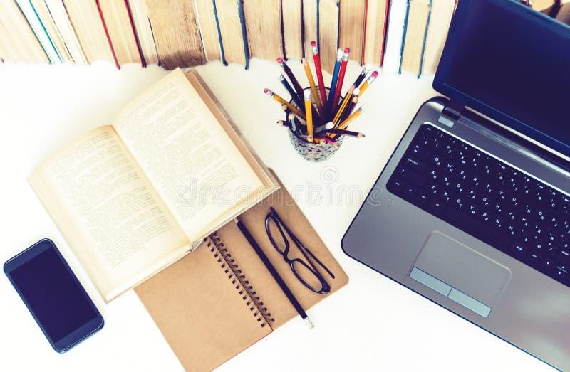 Öppen lärobok, anteckningsbok, smartphone, bärbar datordator, bunt av bokutbildningsbaksida till skolabakgrund, exponeringsglas o fotografering för bildbyråer